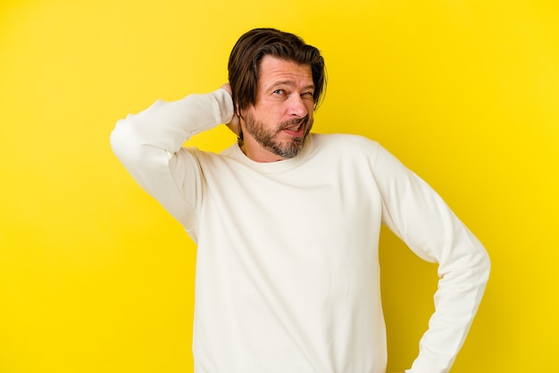 Homem caucasiano de meia-idade, isolado em um fundo amarelo, cansado e com muito sono, mantendo a mão na cabeça.