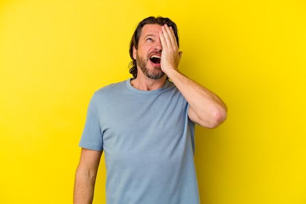 Homem caucasiano de meia-idade isolado em um fundo amarelo, esquecendo de algo, batendo na testa com a palma da mão e fechando os olhos.