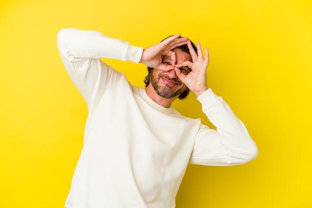 Homem caucasiano de meia-idade, isolado em um fundo amarelo, mostrando sinal de aprovação sobre os olhos