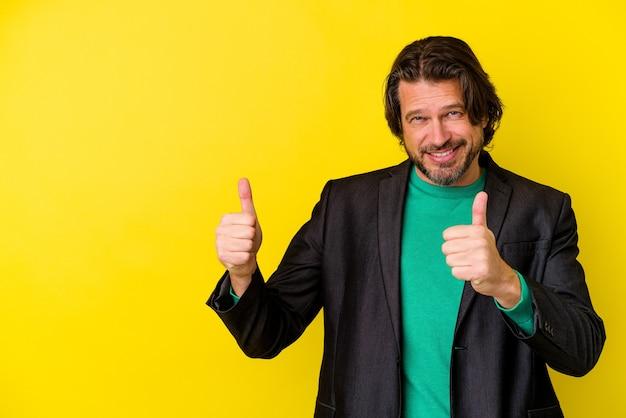 Homem caucasiano de meia-idade isolado em um fundo amarelo, sorrindo e levantando o polegar