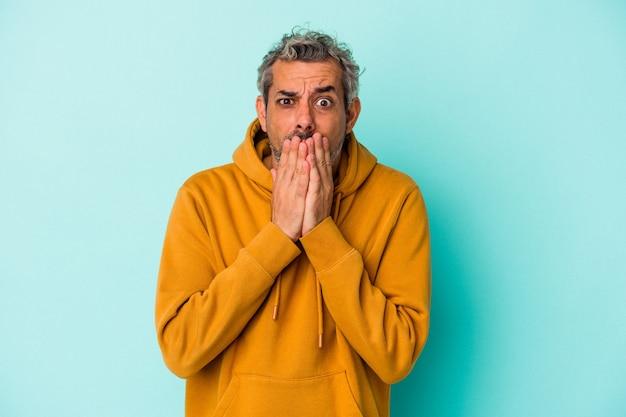 Homem caucasiano de meia-idade isolado em um fundo azul, cobrindo a boca com as mãos parecendo preocupado.