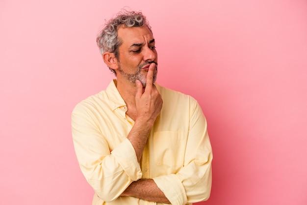 Homem caucasiano de meia-idade, isolado em um fundo rosa, mantendo um segredo ou pedindo silêncio.
