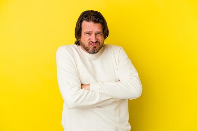 Homem caucasiano de meia-idade isolado na parede amarela, assoando as bochechas, com expressão de cansaço