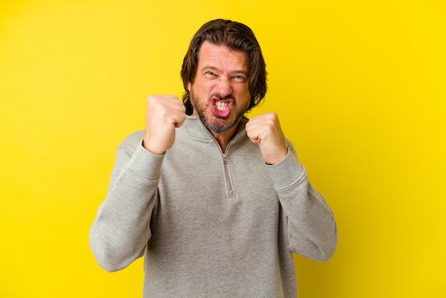 Homem caucasiano de meia-idade, isolado na parede amarela, chateado, gritando com as mãos tensas.
