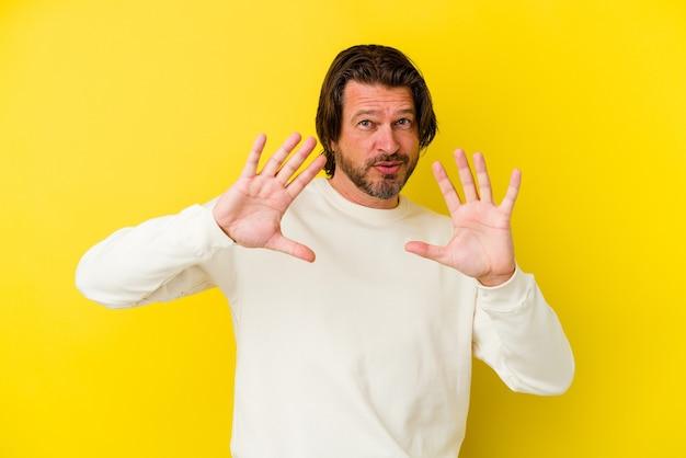 Homem caucasiano de meia-idade isolado na parede amarela rejeitando alguém com um gesto de nojo