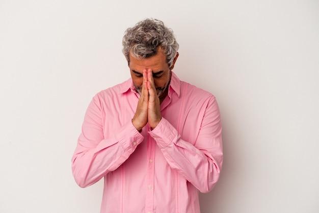 Homem caucasiano de meia-idade, isolado no fundo branco, orando, mostrando devoção, pessoa religiosa em busca de inspiração divina.