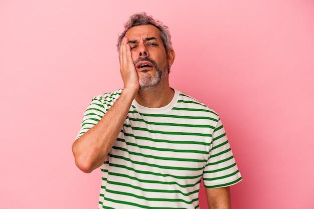 Homem caucasiano de meia-idade isolado no fundo rosa, cansado e com muito sono, mantendo a mão na cabeça.