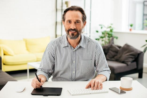 Homem caucasiano de meia-idade positivo sorrindo enquanto está sentado à mesa com o teclado sem fio e a mesa digitalizadora na frente dele