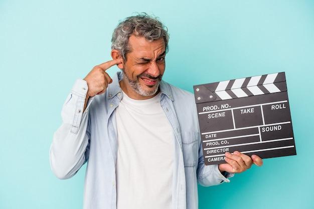 Homem caucasiano de meia-idade segurando uma claquete isolada em um fundo azul, cobrindo as orelhas com as mãos.