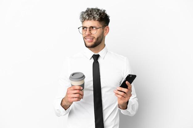 Homem caucasiano de negócios isolado no fundo branco segurando um café para levar e um celular enquanto pensava em algo