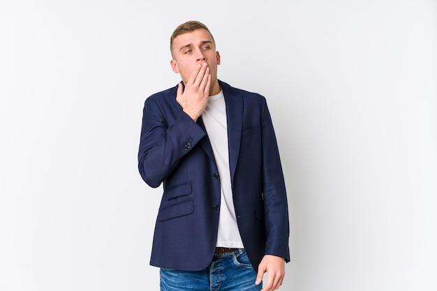Homem caucasiano de negócios jovem bocejando mostrando um gesto cansado, cobrindo a boca com a mão.