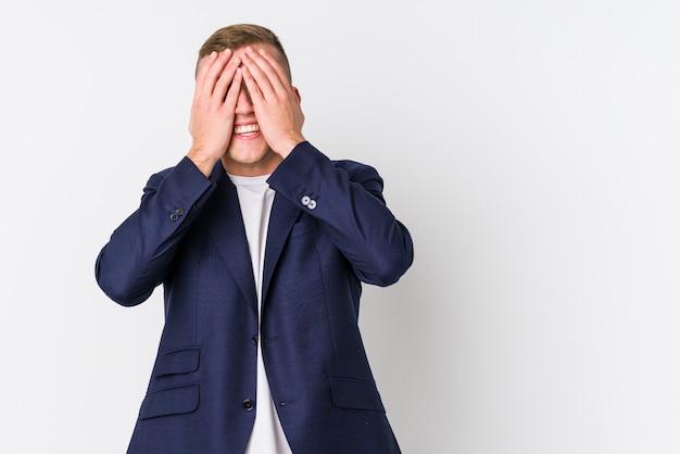 Homem caucasiano de negócios jovem cobre os olhos com as mãos, sorri amplamente esperando por uma surpresa.