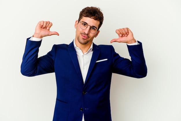 Homem caucasiano de negócios jovem isolado na parede branca se sente orgulhoso e autoconfiante, exemplo a seguir.