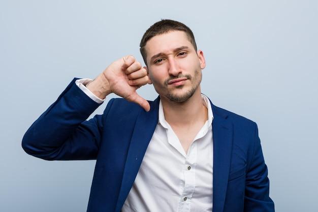 Homem caucasiano de negócios jovem mostrando um gesto de antipatia, polegares para baixo. conceito de desacordo.