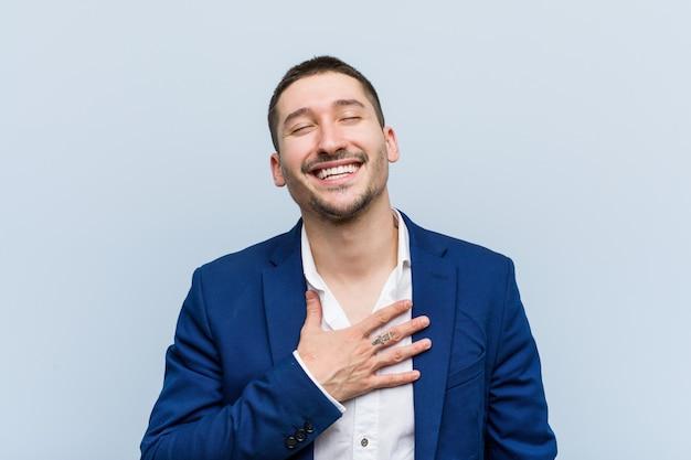 Homem caucasiano de negócios jovem ri em voz alta, mantendo a mão no peito.