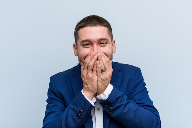 Homem caucasiano de negócios jovem rindo de algo, cobrindo a boca com as mãos.
