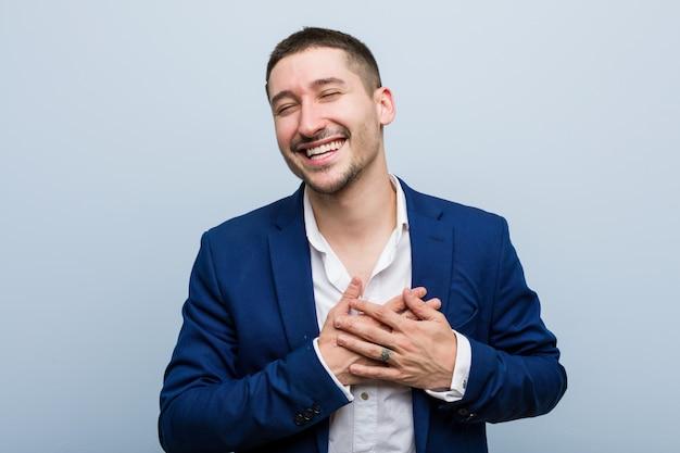 Homem caucasiano de negócios jovem rindo mantendo as mãos no coração, de felicidade.