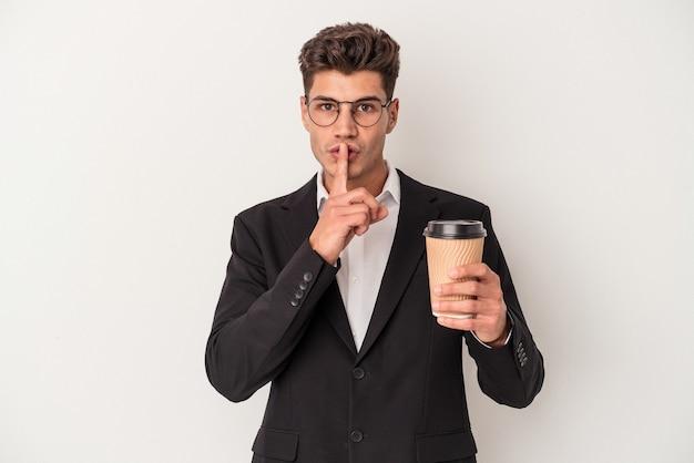 Homem caucasiano de negócios jovem segurando café levar embora isolado no fundo branco, mantendo um segredo ou pedindo silêncio.