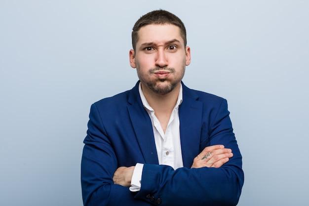 Homem caucasiano de negócios jovem sopra as bochechas, tem expressão cansada. conceito de expressão facial.