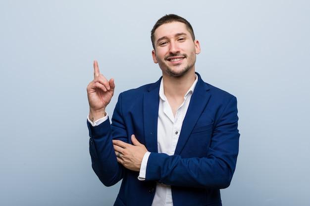 Homem caucasiano de negócios jovem sorrindo alegremente apontando com o dedo indicador fora.