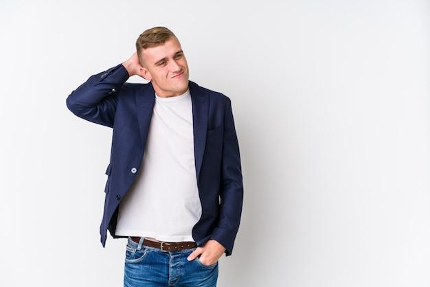 Homem caucasiano de negócios jovem tocando a nuca, pensando e fazendo uma escolha.