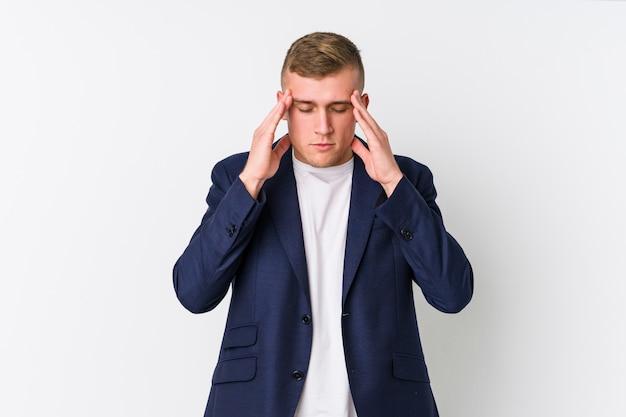 Homem caucasiano de negócios jovem tocando os templos e tendo dor de cabeça.