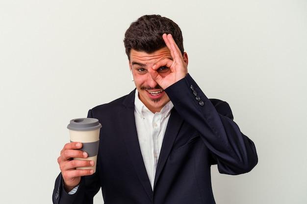 Homem caucasiano de negócios jovem usando fones de ouvido sem fio e segurando tomar café isolado no fundo branco animado, mantendo o gesto ok no olho.