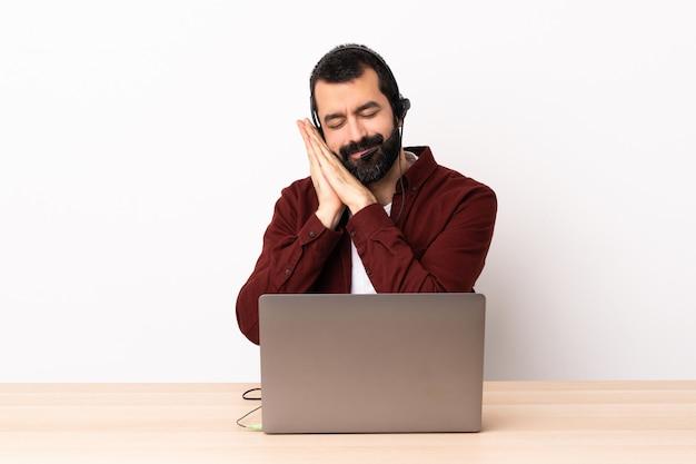 Homem caucasiano de operador de telemarketing trabalhando com um fone de ouvido e com o laptop, fazendo o gesto do sono na expressão dorable.