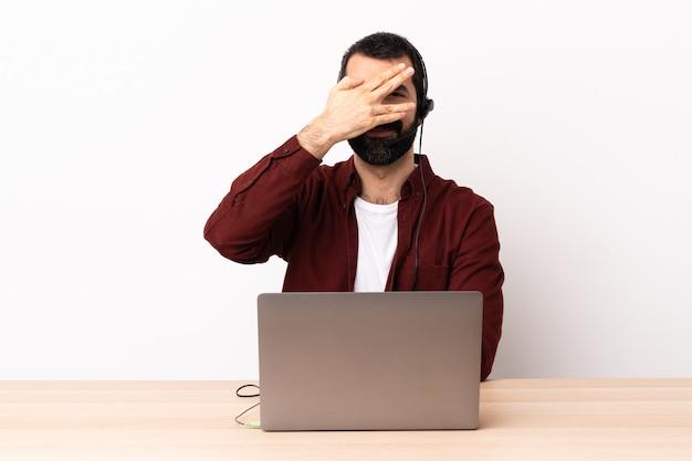 Homem caucasiano de operador de telemarketing trabalhando com um fone de ouvido e com olhos de coning laptop pelas mãos e sorrindo.