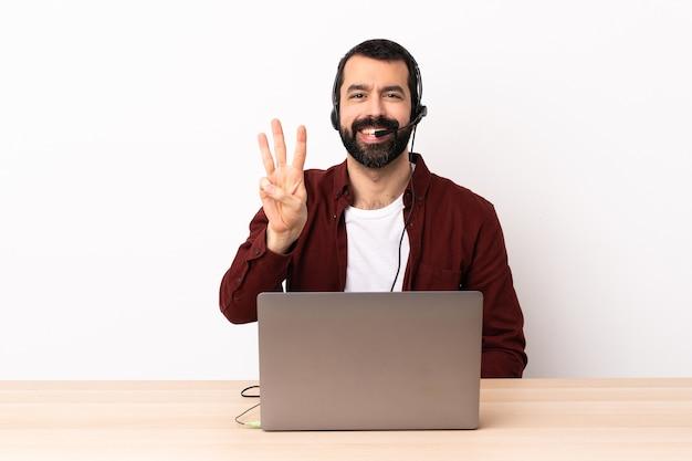 Homem caucasiano de operador de telemarketing trabalhando com um fone de ouvido e um laptop