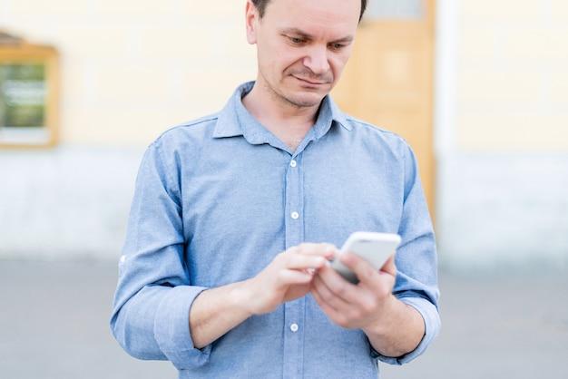 Homem caucasiano de quarenta anos na rua usa o telefone no verão.
