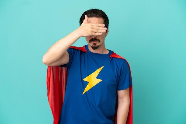 Homem caucasiano de super-herói isolado em um fundo azul, cobrindo os olhos com as mãos. não quero ver nada