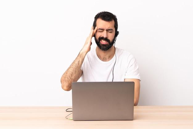Homem caucasiano de telemarketing trabalhando com um fone de ouvido e com laptop com dor de cabeça.