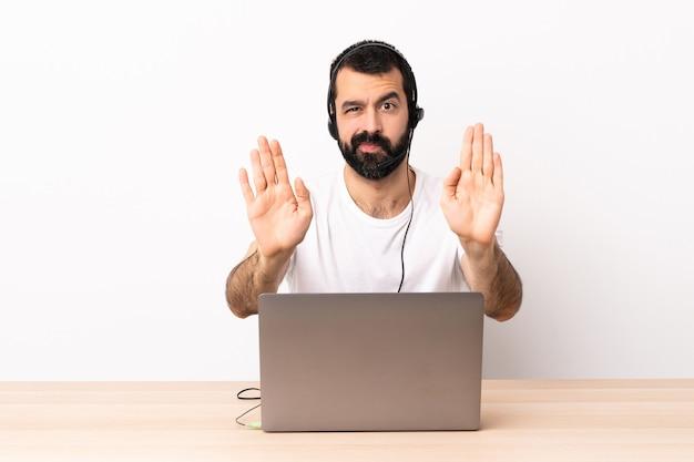 Homem caucasiano de telemarketing trabalhando com um fone de ouvido e com laptop fazendo gesto de pare e decepcionado.