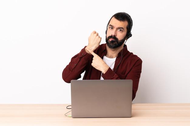 Homem caucasiano de telemarketing trabalhando com um fone de ouvido e com laptop fazendo o gesto de estar atrasado.