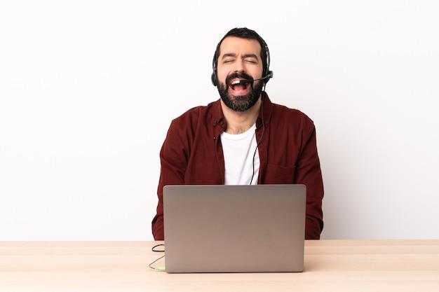 Homem caucasiano de telemarketing trabalhando com um fone de ouvido e com laptop gritando na frente com a boca aberta.