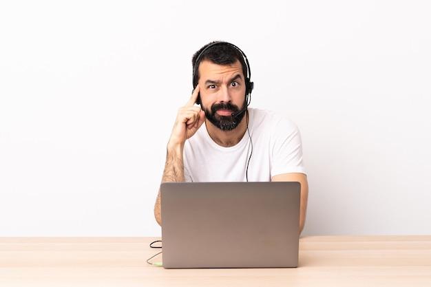 Homem caucasiano de telemarketing trabalhando com um fone de ouvido e com laptop pensando uma ideia.