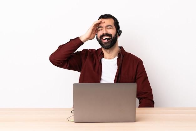 Homem caucasiano de telemarketing trabalhando com um fone de ouvido e com laptop sorrindo muito.