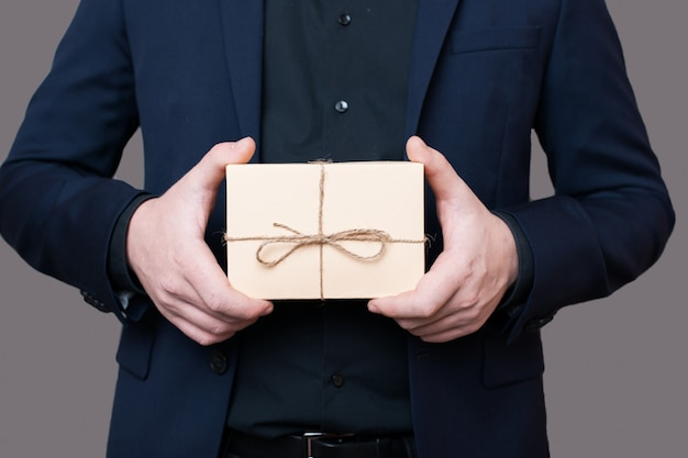 Homem caucasiano de terno segurando um presente nas mãos, posando sem rosto em uma parede cinza com espaço livre