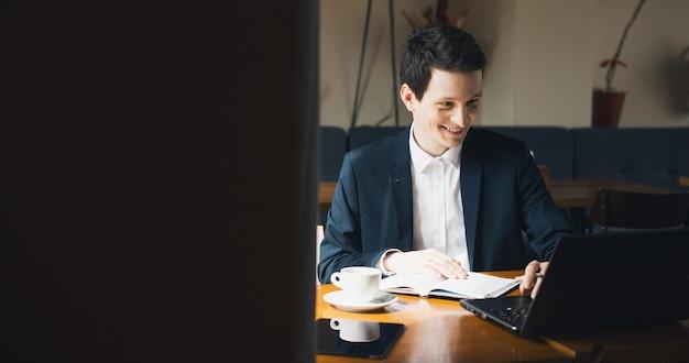 Homem caucasiano de terno trabalhando com o computador e escrevendo um livro enquanto está sentado no escritório