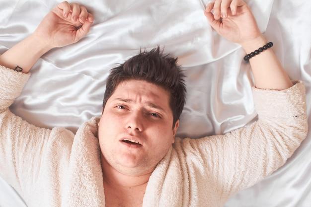 Homem caucasiano deitado na cama branca alta chave, close
