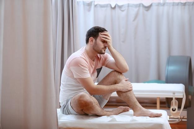 Homem caucasiano deprimido sério novo que senta-se na cama de hospital e que prende sua cabeça.