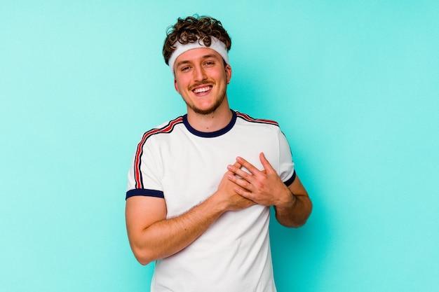 Homem caucasiano do esporte jovem isolado em um fundo azul tem uma expressão amigável, pressionando a palma da mão no peito. conceito de amor.