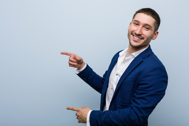 Homem caucasiano do negócio novo excitado apontando com os dedos indicadores ausentes.