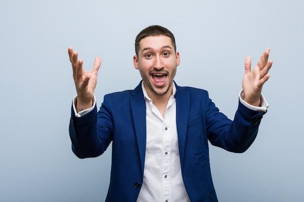 Homem caucasiano do negócio novo que recebe uma surpresa agradável, entusiasmado e levantando as mãos.
