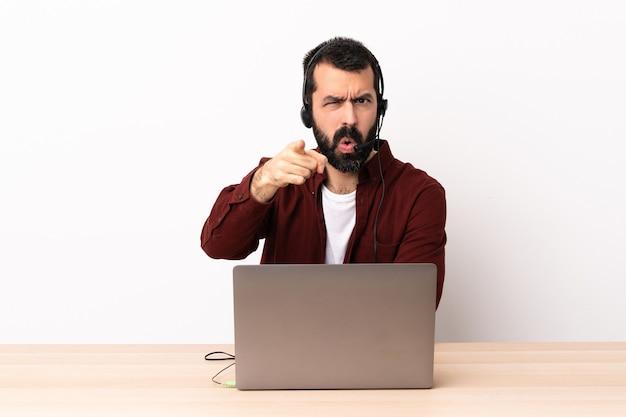 Homem caucasiano do operador de telemarketing trabalhando com um fone de ouvido e com laptop frustrado e apontando para a frente.