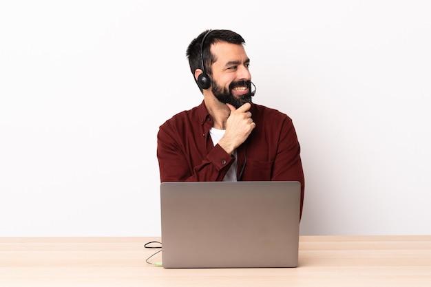 Homem caucasiano do operador de telemarketing trabalhando com um fone de ouvido e com laptop, olhando para o lado e sorrindo.