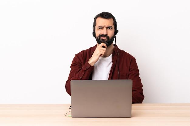 Homem caucasiano do operador de telemarketing trabalhando com um fone de ouvido e com laptop pensando.