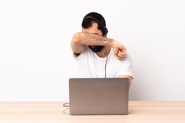 Homem caucasiano do operador de telemarketing trabalhando com um fone de ouvido e com o laptop cobrindo os olhos com as mãos.