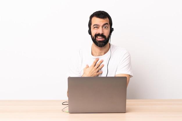 Homem caucasiano do operador de telemarketing trabalhando com um fone de ouvido e um laptop apontando para si mesmo